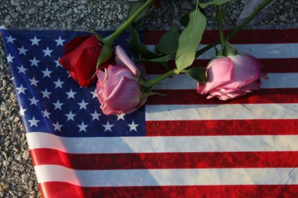 ORLANDO, FL - JUNE 13: Flowers and an American flag are seen on the ground near the Pulse Nightclub where Omar Mateen allegedly killed at least 50 people on June 13, 2016 in Orlando, Florida. The mass shooting killed at least 50 people and injuring 53 others in what is the deadliest mass shooting in the country's history. (Photo by Joe Raedle/Getty Images)